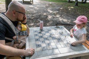 Tėtis parke žaidžia su dukrele akmenukų šaškėm, ant krūtinės nešyklėje kelių mėnesių dukrytė