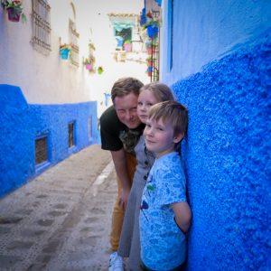 Tėtis stovi prie mėlynos sienos su dviem vaikais - mergaite ir berniuku.