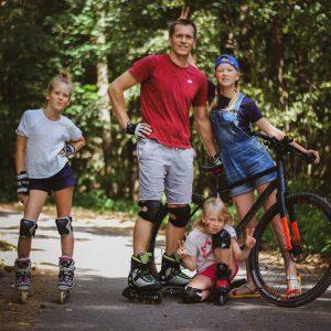 Tėtis su dviem dukromis važinėjasi riedučiais, trečioji važiuoja dviračiu.