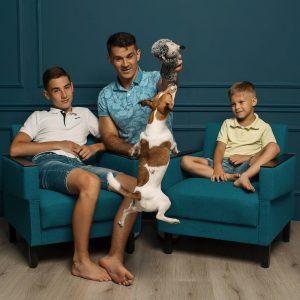 Tėtis su dviem sūnumis sėdi ant fotelių. Tetis laiko rankose žaisliuką, kurį pagriebti pašokęs šuniukas