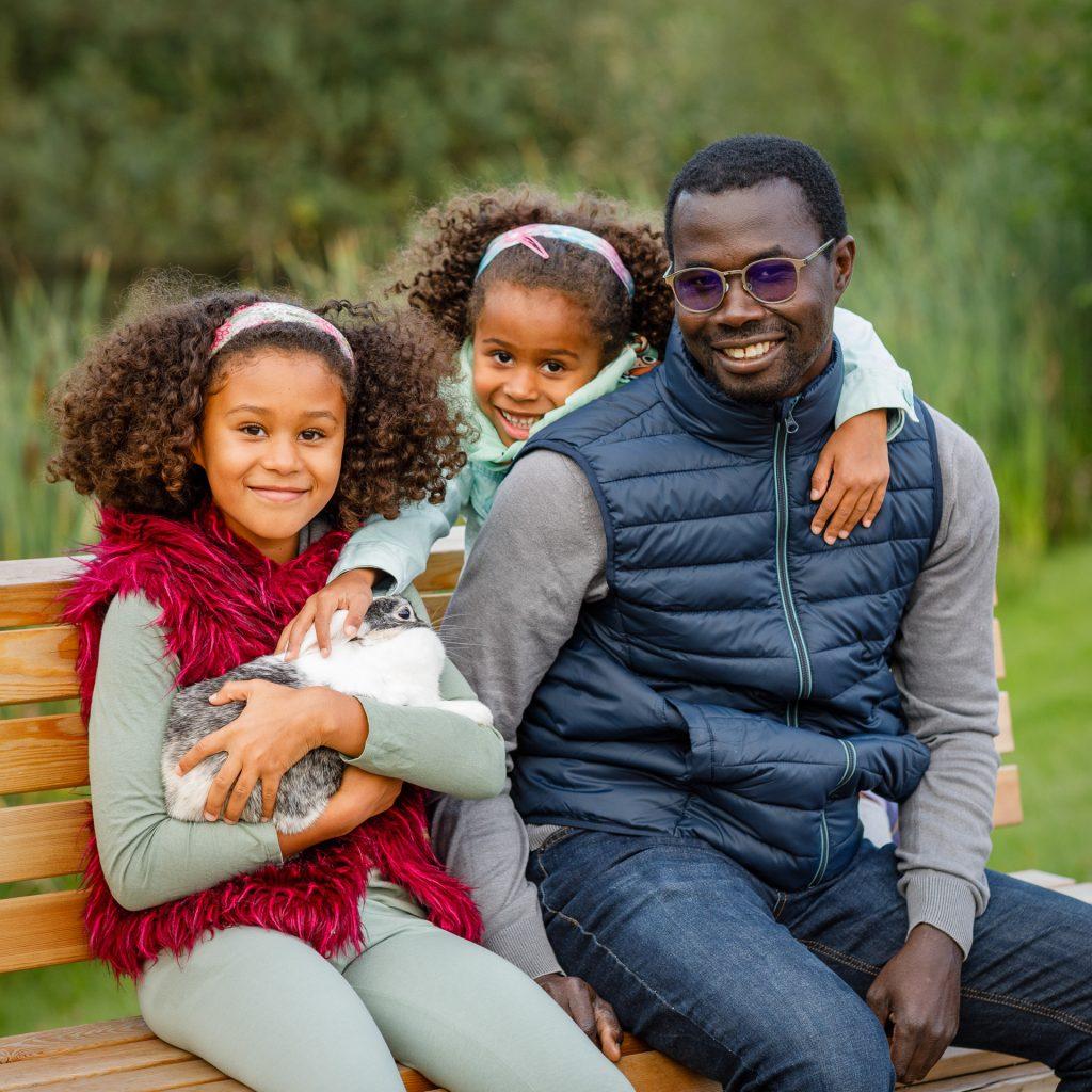 Juodaodis tėtis su dviem dukrom parke ant suoliuko