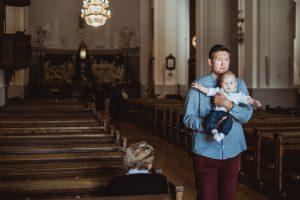 Tėtis ant rankų neša sūnų po krikštynų bažnyčioje